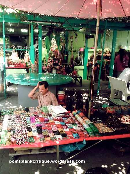 Thai Superstition Vendor selling trinkets outside at the temple grounds
