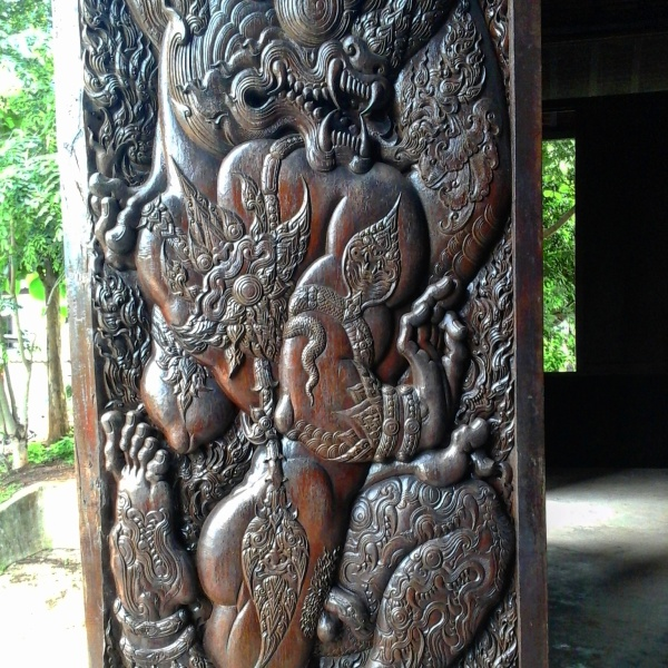IBeautifully carved wooden door panels in the main building of Baan Daam
